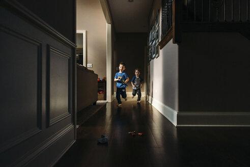 Siblings running in hallway at home - CAVF27495
