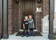Portrait of boys standing against door - CAVF27498