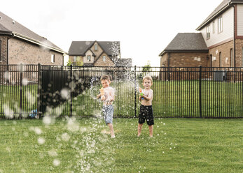 Portrait of boys squirting with water gun in backyard - CAVF27501
