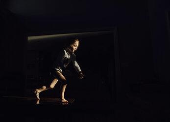 Boy running in dark room at home - CAVF27507
