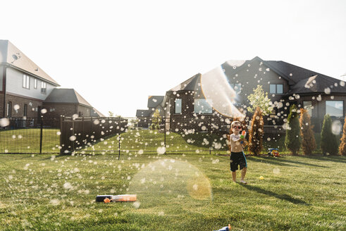 Boy playing with water gun at backyard - CAVF27519