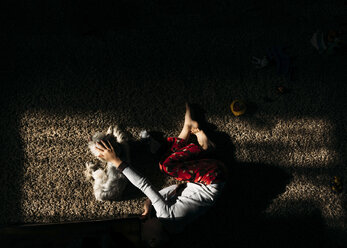 Overhead view of boy sleeping on rug with dog at home - CAVF27525