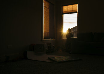 Silhouette of boy looking through window at home - CAVF27528