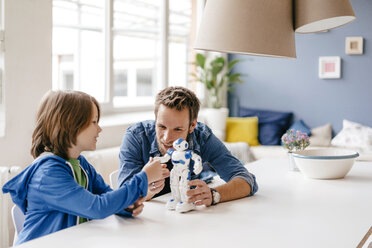 Happy father and son playing with robot on table at home - KNSF03581
