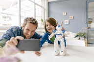 Happy father and son taking a selfie with robot on table at home - KNSF03584