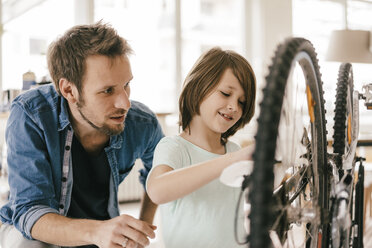Father and son repairing bicycle together at home - KNSF03587