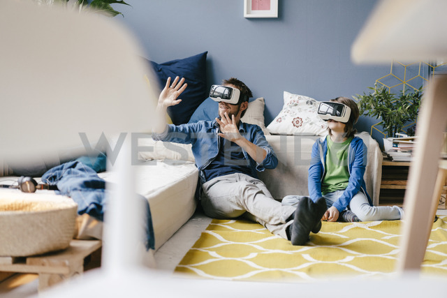 Father and son wearing VR glasses sitting on the floor at home - KNSF03596