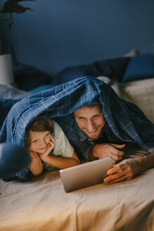 Happy father and son watching a movie on tablet under blanket - KNSF03605