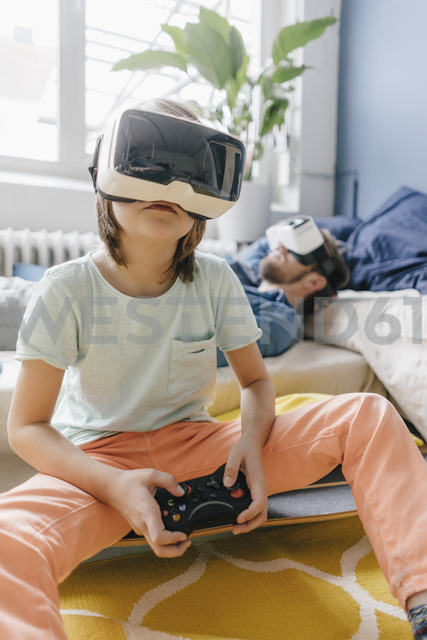 Boy and father wearing VR glasses playing video game at home - KNSF03614