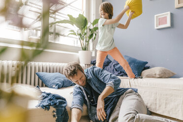 Father and son having a pillow fight at home - KNSF03617