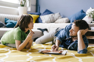 Father and son eating pizza on the floor at home - KNSF03620