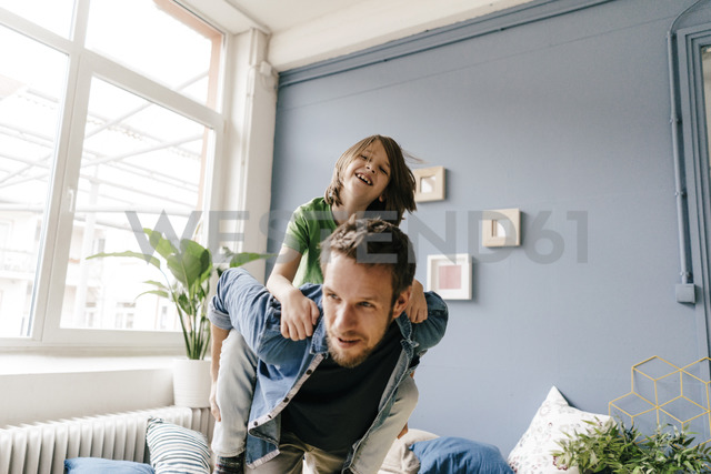 Happy father carrying son piggyback at home - KNSF03629