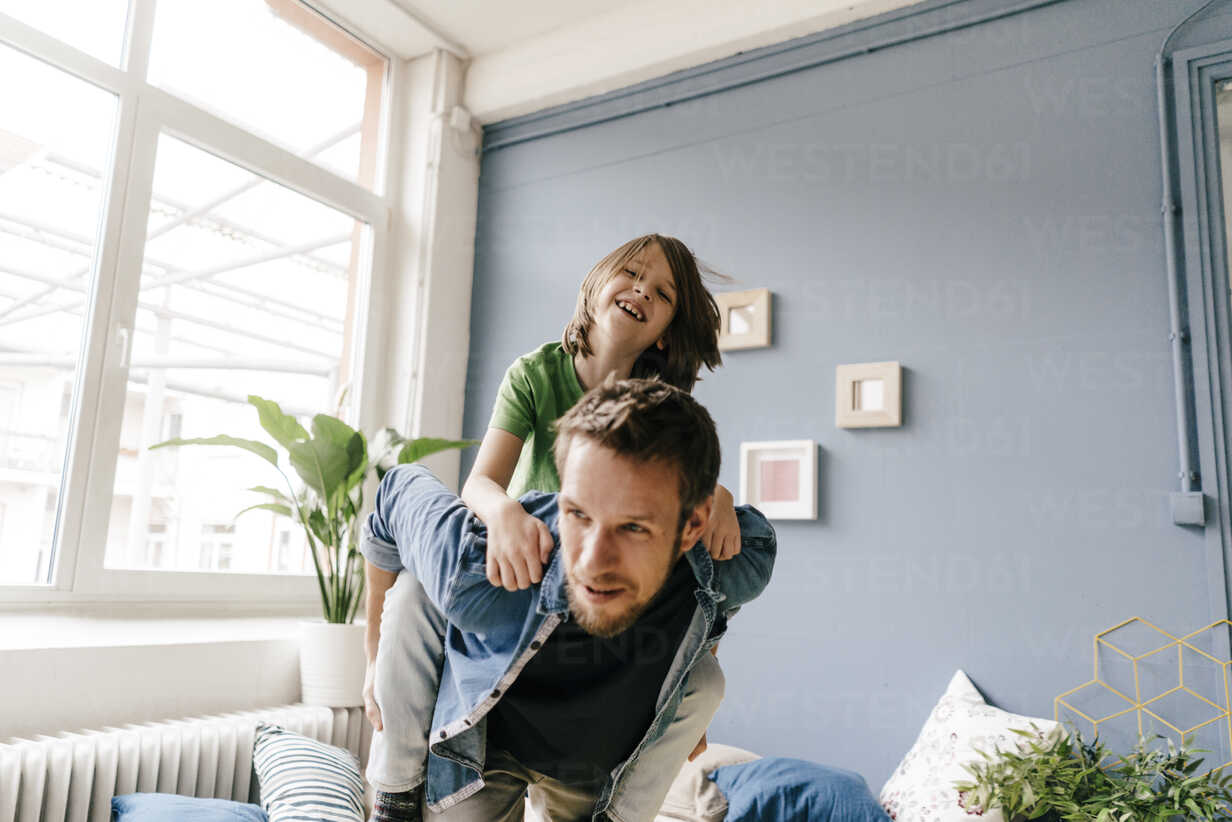 Happy father carrying son piggyback at home - KNSF03629 - Kniel Synnatzschke/Westend61