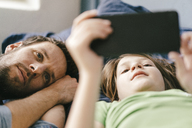 Father and son looking at smartphone together at home - KNSF03632