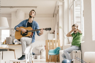 Horrified son covering his ears with father playing guitar at home - KNSF03635