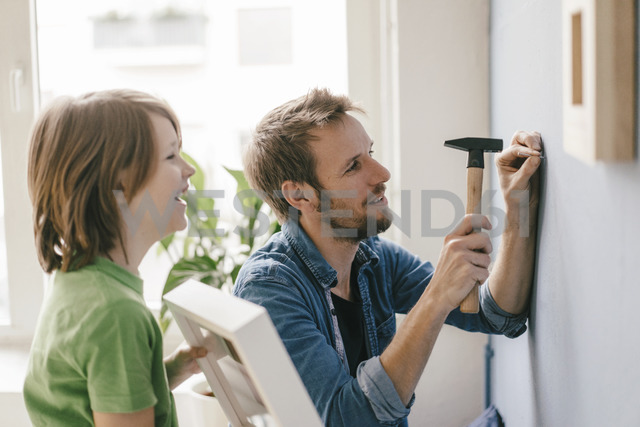 Son watching father driving a nail into the wall at home - KNSF03641 - Kniel Synnatzschke/Westend61