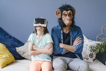 Father wearing monkey mask sitting next to son wearing VR glasses at home - KNSF03647