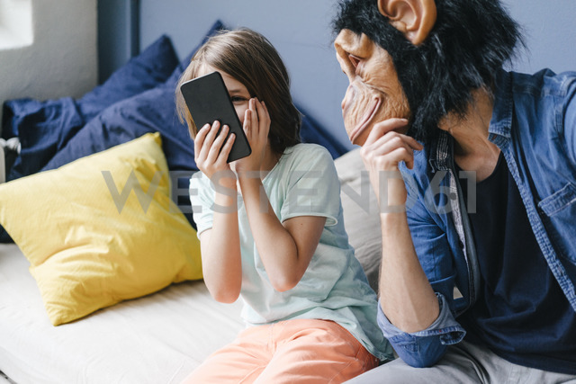 Father wearing monkey mask looking at son using smartphone at home - KNSF03650
