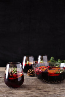 Close-up of drinks with fruits and pine cone on wooden table against black background - CAVF27599