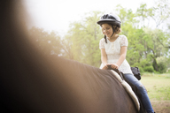 Happy girl horseback riding at farm - CAVF27629
