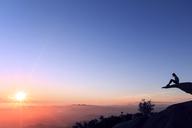Woman sitting on Mt. Woodson against sky - CAVF27638