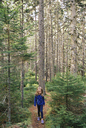 Girl walking on dirt road in forest - CAVF27734