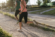 Low section of young couple jogging at park - CAVF27752