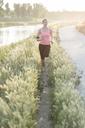Sportswoman jogging amidst plants in park - CAVF27755