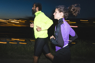 Side view of young couple jogging on footpath during night - CAVF27767