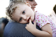 Portrait of cute girl with finger in mouth being carried by mother outdoors - CAVF27803
