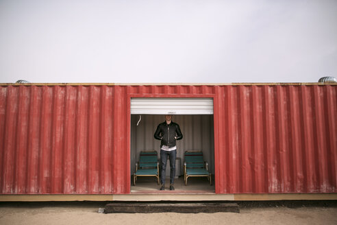 Low section of man standing in red container - CAVF27806