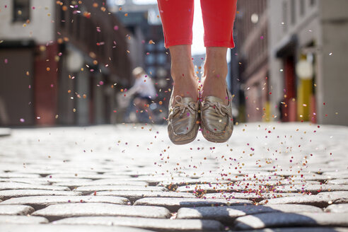 Low section of woman with confetti jumping on cobble street during sunny day - CAVF27827