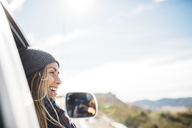 Smiling young woman riding in car against sky - CAVF27905