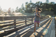 Woman running on wooden bridge against clear sky - CAVF27950