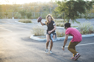 Happy friends playing with American football at parking lot - CAVF27959