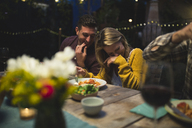 Happy couple sitting at table while enjoying dinner party with friends - CAVF28013