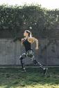 Full length side view of determined female athlete running at park - CAVF28049