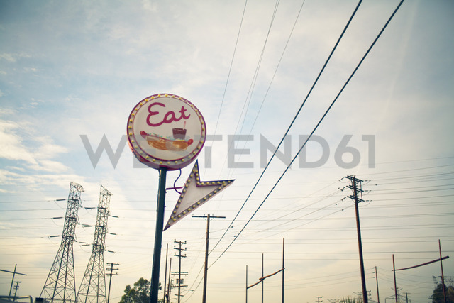 Low angle view of commercial sign and electricity pylons against sky - CAVF28109