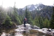 Hiker and dog walking on rocks by Snow Lake against mountains - CAVF28115