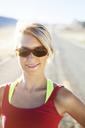 Portrait of happy sportswoman on country road - CAVF28118