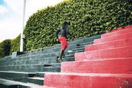 Rear view of sportswoman running on steps in stadium - CAVF28175