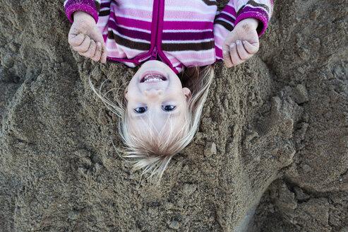 Overhead portrait of girl lying on sandy beach - CAVF28328