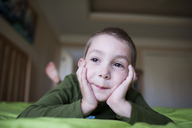 Close-up of thoughtful boy lying on bed at home - CAVF28337
