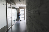 Businessman standing at the window holding cell phone - UUF13085