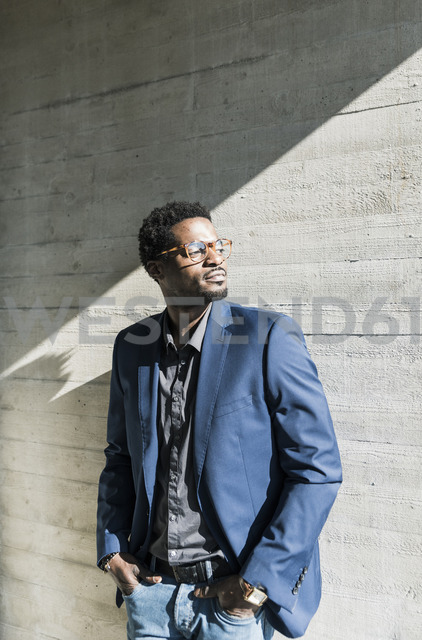 Businessman standing in sunshine at concrete wall looking away - UUF13094