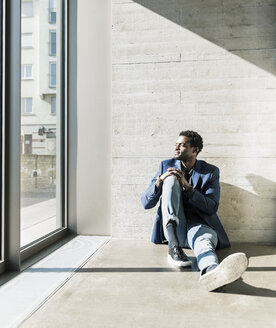 Businessman sitting on the floor in sunshine looking out of window - UUF13097