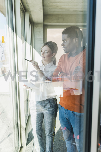 Casual businesswoman and businessman discussing paper at the window - UUF13112