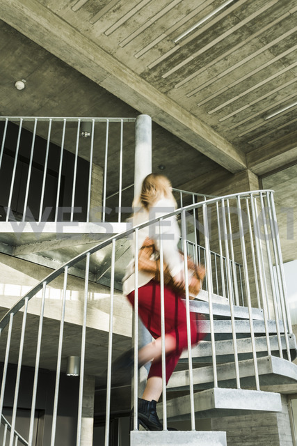 Businesswoman rushing upstairs - UUF13124