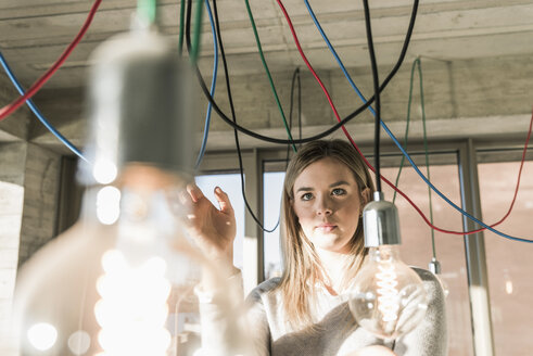 Young businesswoman in office examining cables at light bulbs - UUF13127
