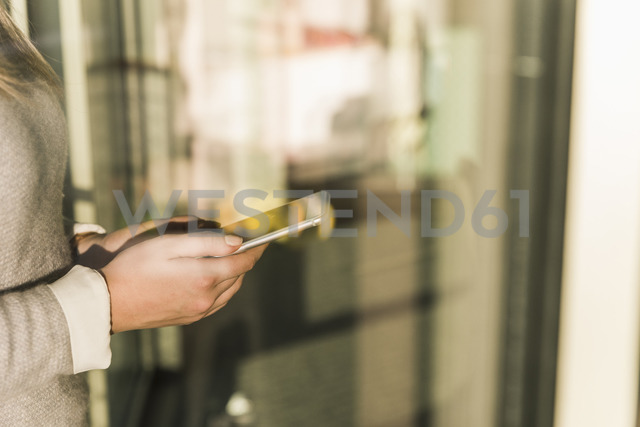 Close-up of businesswoman holding cell phone - UUF13130